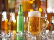 Bottle of beer with glass on bar desk Royalty Free Stock Photography