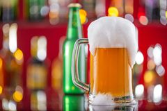 Bottle of beer with glass on bar desk Stock Photography