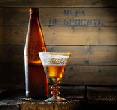 A bottle of beer and a glass of the original form with a frothy cold beer on a wooden background. A bottle of beer and a glass of the original form with a frothy Royalty Free Stock Photo