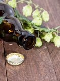 Bottle of Beer with Hops on wood Stock Photography