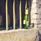 Bottle of beer left on the windowsill of an old window Royalty Free Stock Photo