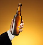 Bottle of beer in a man's hand Stock Images