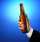 Bottle of beer in a man's hand Royalty Free Stock Images