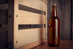 A bottle of beer next to a wooden box Stock Photos
