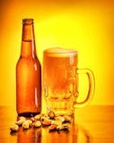 Bottle of beer and nuts. Bottle and glass full of beer with pistachio nuts on the table on yellow background, october beer fest, tasty alcoholic drink royalty free stock photo
