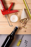 Bottle of beer, pistachio nuts and work tools on wooden planks. Flat lay, top view. Stock Images