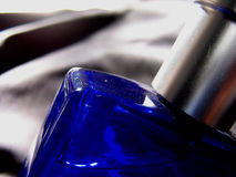 Bottle in Blue. A blue perfume bottle on a black fabric Royalty Free Stock Photos