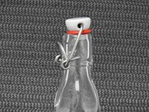 Bottle with bracket closure. On a black woven background stock images