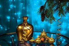 Bottle of brandy and candles with Christmas tree branches on blue background Royalty Free Stock Photos