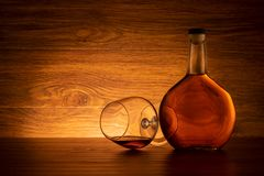 Bottle of brandy with wine glass on wooden background stock photos