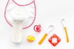 Bottle with breastmilk and infant formula powdered healthy food, toys and bib on white background top view. Bottle with breastmilk and infant formula powdered Stock Images