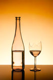 Bottle and broken glass. Bottle and a broken wine glass - filled to the same level royalty free stock image