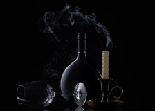 Bottle, candle and glass of wine on black background Royalty Free Stock Photos