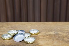 Bottle caps on rustic wooden background Royalty Free Stock Photo