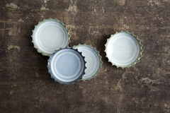 Bottle caps on rustic wooden background Royalty Free Stock Photography