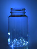 Bottle with capsules. In the blue light Royalty Free Stock Image