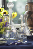 Bottle, carafe and glasses. Empty glass recipients on a table, interior day Royalty Free Stock Photography