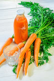 Carrot juice still life. A bottle of carrot juice with empty glass and some fresh carrots on white wood table. Still life of a healthy eating concept Royalty Free Stock Photos