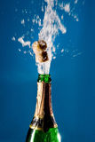 Bottle of champagne. With a popping cork (against a blue background royalty free stock image