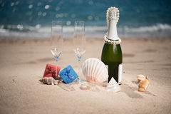Bottle of champagne on the beach with a gift  boxes and shells. Bottle of champagne on the beach with a gift red and blue boxes and shells Royalty Free Stock Photography