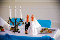 Bottle champagne the bride and groom. Wedding table decorated. Wedding. The decoration of the table. The scenery. Marriage. Festive day. The wedding decoration Stock Photos