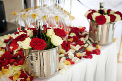 Bottle of champagne in a bucket with flowers. Near pyramid of glasses Stock Image