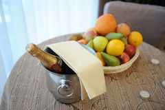 Bottle of champagne in a bucket and fruit platter served on table Royalty Free Stock Photos