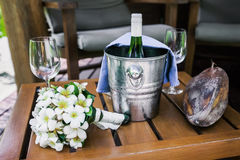 Bottle of champagne in bucket and glasses. Bottle of champagne in bucket, glasses with frangipani and old mago fruit on a wooden chair Stock Images