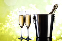 Bottle of champagne. Champagne bottle in bucket with glasses of champagne in front of green bokeh background Stock Images