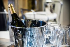 Bottle of champagne in a bucket and glasses of wine. Focus on the bottle, soft focus Royalty Free Stock Photo