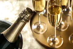Bottle of champagne in bucket with ice and glasses on table, closeup. Space for text stock photos