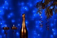 Bottle of champagne and candles with Christmas tree branches on blue background Stock Photography