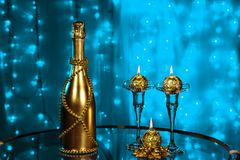 A bottle of champagne and candles in New year and Christmas on blue background Stock Images