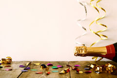 Bottle of champagne and colorful confetti Stock Images
