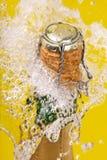 Bottle of champagne, cork and splashing. Bottle of champagne popping its cork and splashing royalty free stock photography