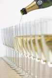 Bottle of champagne filling row of glasses selective focus Stock Images