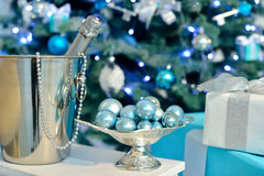 Bottle champagne in front of decorated christmas tree with blue vintage balls and light., gift boxes. Royalty Free Stock Images