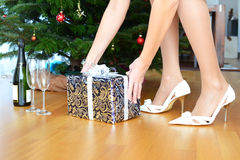 Bottle of champagne and a gift. Under the Christmas tree Stock Photography