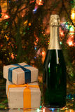 Bottle of champagne with a gift box on the background lights Royalty Free Stock Photos