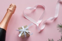 Merry Christmas and Happy New Year. Pink background. Bottle champagne with gift and pink ribbon in the shape heart. Present with love. Christmas concept vector illustration