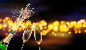 Bottle of champagne with glass over blur background. Splashing bottle of champagne with glass over blur colored spot background. Celebration concept, free space Royalty Free Stock Photos