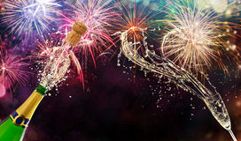 Bottle of champagne with glass over fireworks background royalty free stock photos