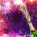 Bottle of champagne with glasses over fireworks background. Splashing bottle of champagne with glasses over blur colored background. Celebration concept, free Stock Images