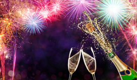 Bottle of champagne with glasses over fireworks background. Splashing bottle of champagne with glasses over fireworks background. Celebration concept, free space royalty free stock image