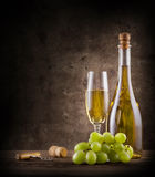 Bottle of champagne with grapes and glass Stock Image