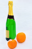 Bottle of champagne and  oranges in the snow Stock Photos