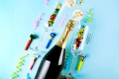 Bottle of champagne, pair of flute glasses, streamers, candles & other party attributes on bright pink paper background. Speech royalty free stock image