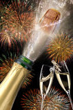 Bottle of champagne with popping cork at new years 2017. Bottle of champagne with popping cork and cascade firework at new years Stock Photo
