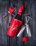 Bottle of champagne in red paper, heart on blue wooden background Stock Image