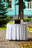 The bottle of champagne and snacks are on white round table in t Royalty Free Stock Image